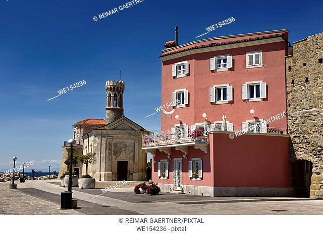 Red stucco apartment on the Adriatic Sea coast at Piran Slovenia next to the Punta lighthouse and 13th century Church of St Clement