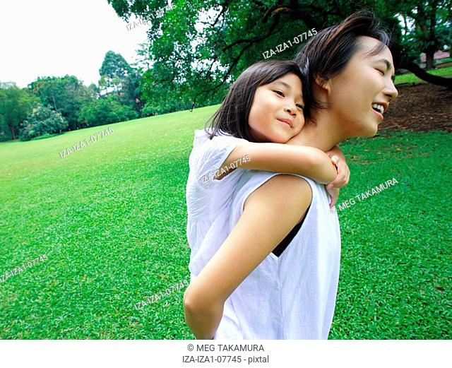Side profile of a girl riding piggyback on her mother in a park