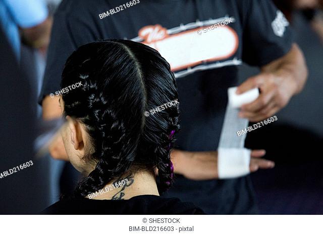 Man wrapping hand near Caucasian girl wearing braids