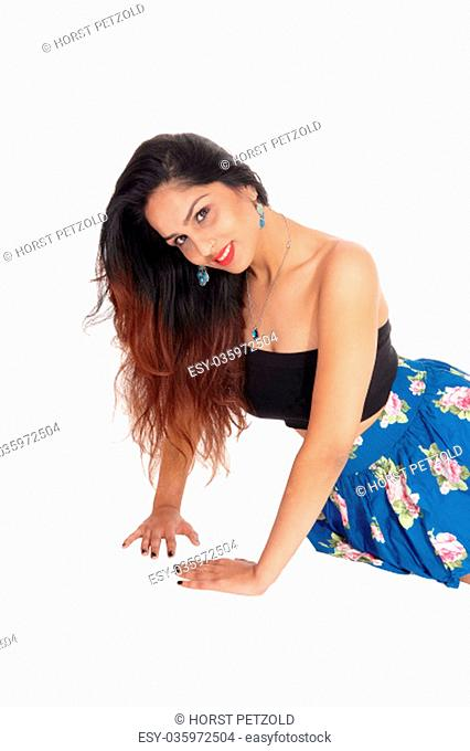 A young beautiful woman with long brunette hair and a blue skirt.and black corset sitting on the floor, isolated for white background