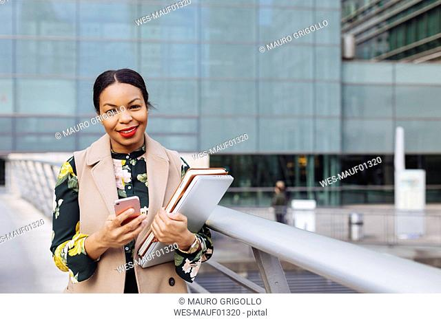 UK, London, portrait of fashionable businesswoman with cell phone, laptop and notebook
