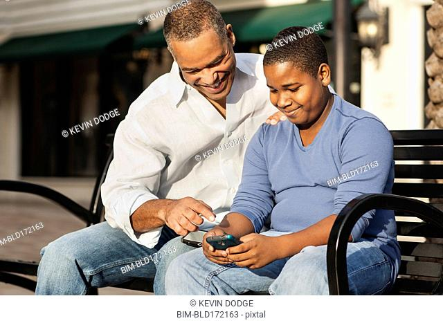 African American father and son using cell phone on bench