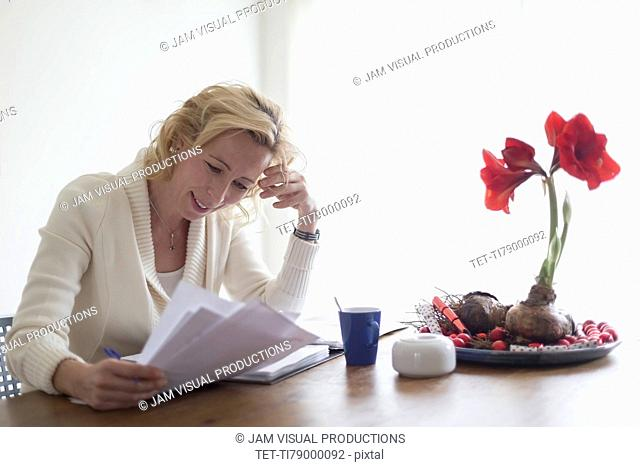 Businesswoman sitting at table at home and reading documents