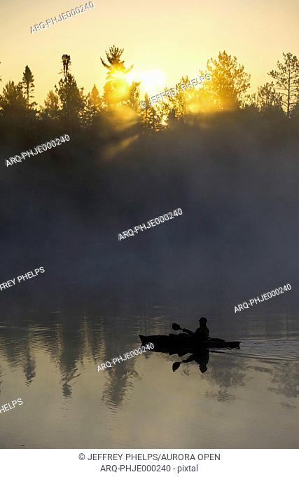 A kayaker enjoys the sunrise as steam rises from Lake Pleasant in Conover, Wisconsin on a brisk fall morning