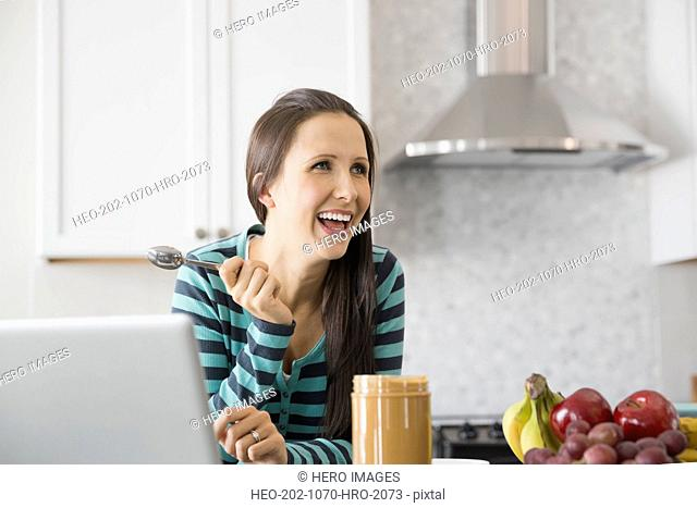 Pregnant woman with peanut butter in kitchen
