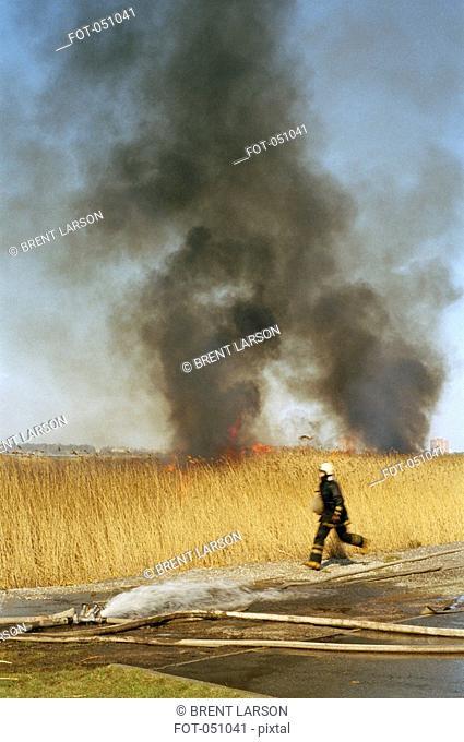 A firefighter running from a blazing field