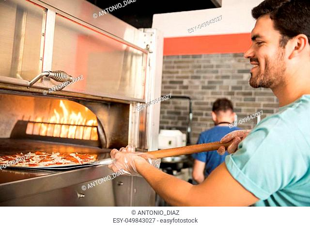 Close-up portrait a cheerful chef wearing gloves putting raw prepared pizza in oven using peel in pizza shop