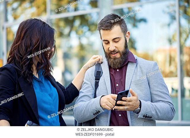Businessman and businesswoman with cell phone outdoors