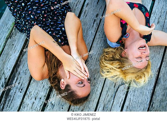 Panama, Bocas del Toro, Two laughing women lying on wooden jetty