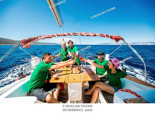 Men and young women on board yacht raising a toast with sliced water melon, Croatia