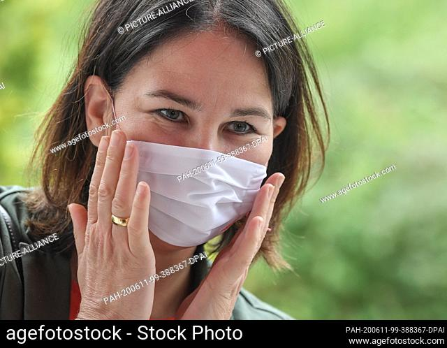 11 June 2020, Brandenburg, Eberswalde: Annalena Baerbock, federal chairwoman of Bündnis 90/Die Grünen, puts on a mouth-nose protection mask before visiting the...