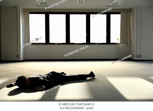 Young Japanese businessman dead on the floor of an empty office