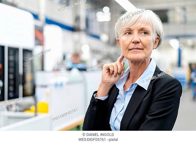 Portrait of senior businesswoman in a factory looking around