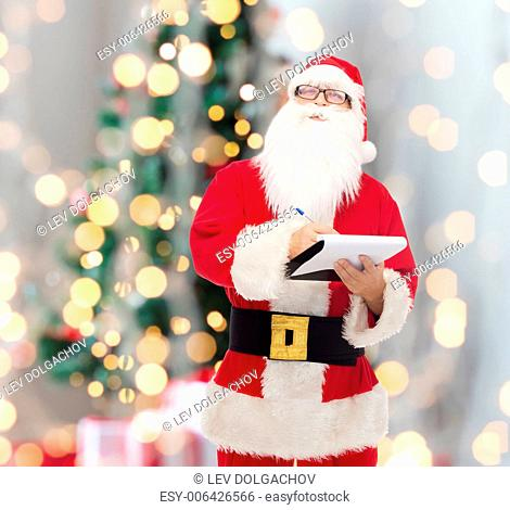 christmas, holidays and people concept - man in costume of santa claus with notepad and pen over tree lights background