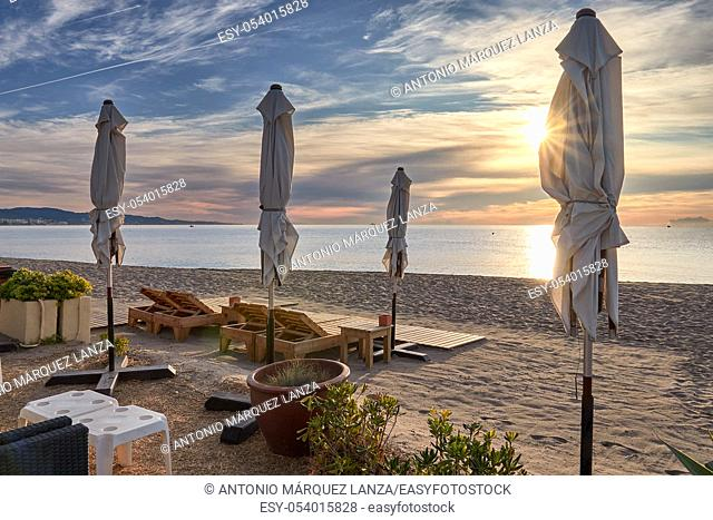 beach lounger at sunrise with parasol
