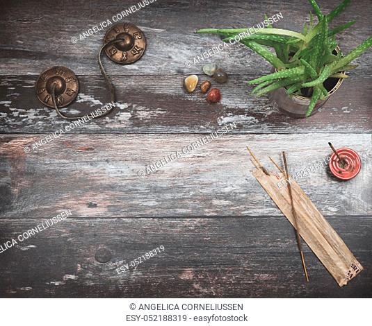 Rustic wooden table for text copy, with green aloe vera plant, burning incense, incense sticks, small rounded energy healing stones in earthy colors and Tibetan...