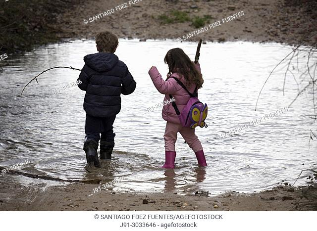 Brother and sister playing in puddle. Madrid province, Spain