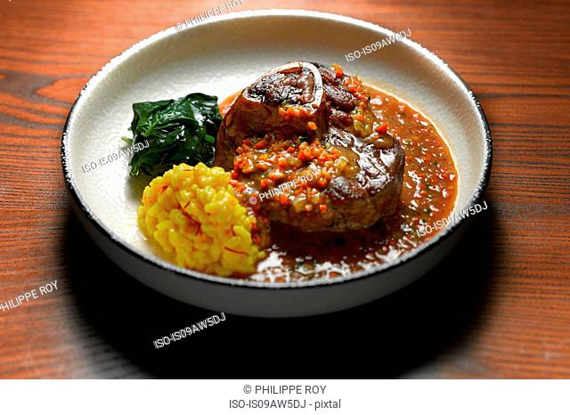 High angle view of ossobuco with side dish of vegetables in shallow bowl