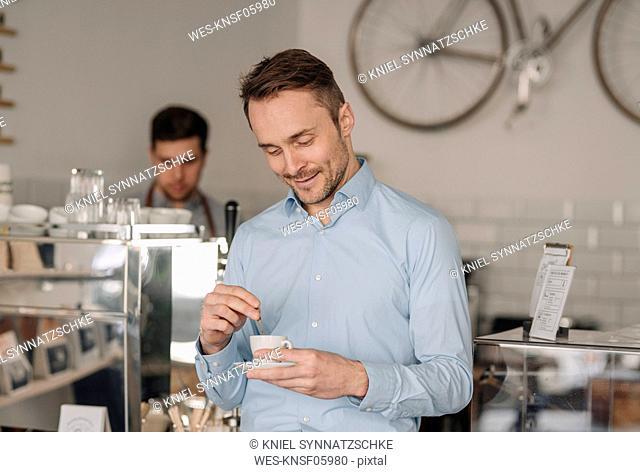 Businessman drinking fresh coffee in a coffee shop, smiling