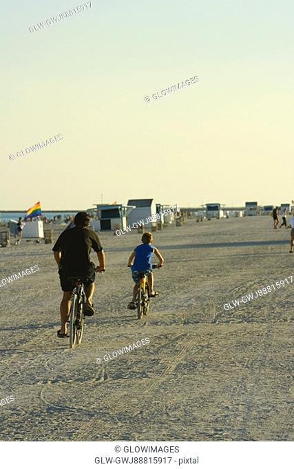 Rear view of a man and a child cycling on the beach