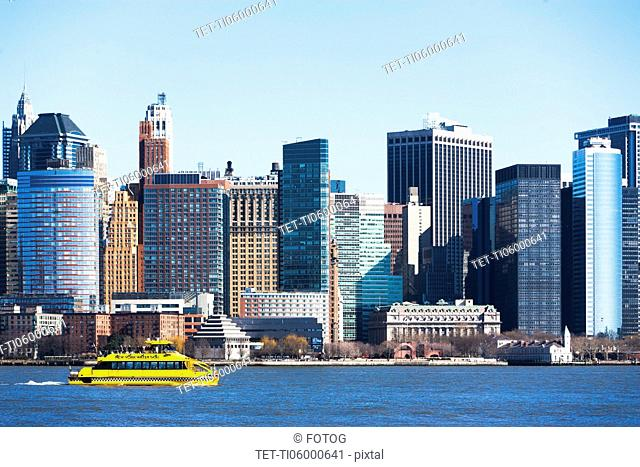 USA, New York State, New York City, Manhattan, City panorama with water taxi passing by