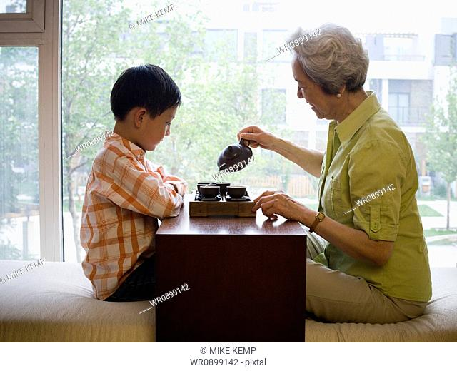 Grandmother and grandson sitting cross legged drinking tea