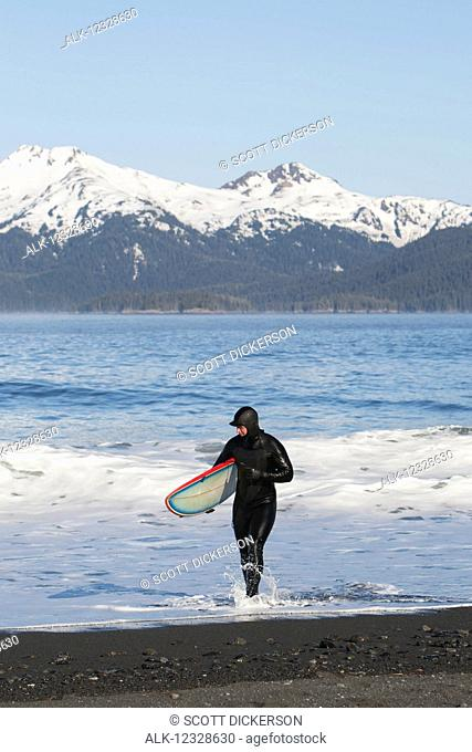 Surfer walking in the water on the Kenai Peninsula Outer Coast, South-central Alaska; Alaska, United States of America