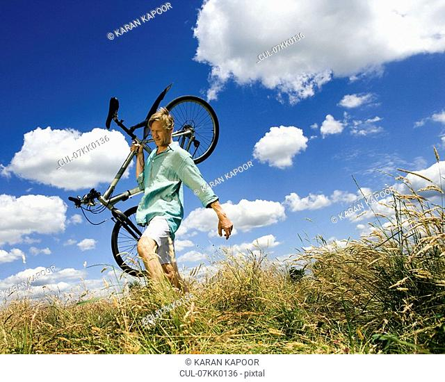 Man carrying cycle across field