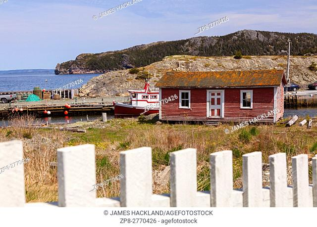 An old dilapidated shed and a fishing vessel. Brigus, Newfoundland, Canada