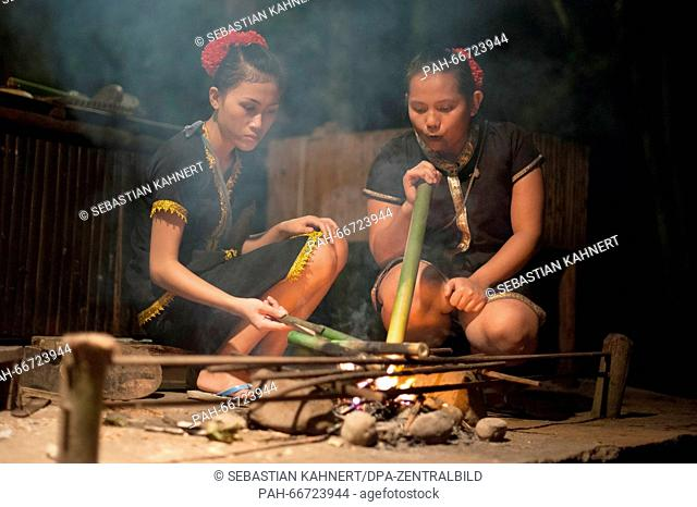 Two women wearing traditional costumes are sitting at a campfire at the Mari Mari Cultural Village near Kota Kinabalu, Malaysia, on 27 October 2014