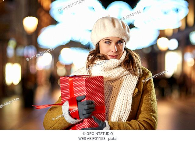 Portrait of smiling woman with Christmas present in the evening