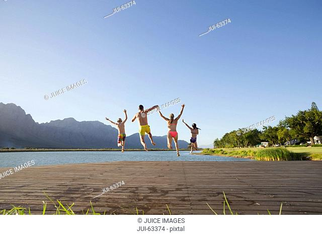 Family jumping into lake from a jetty