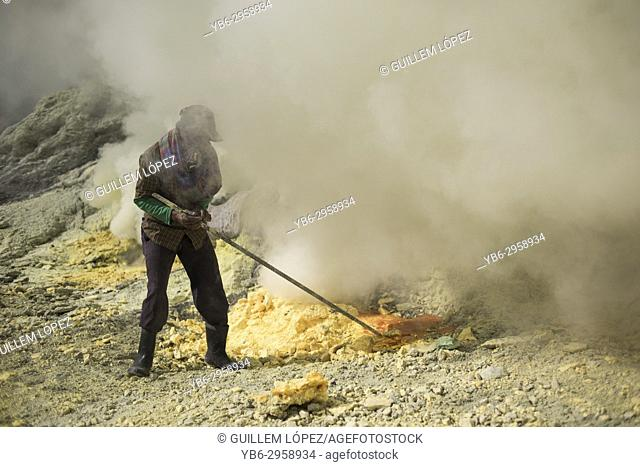 A miner extracting sulfur from the Kawah Ijen Volcano crater, East Java, Indonesia