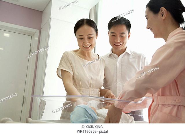 Young happy family with nurse looking down at their newborn in the hospital nursery