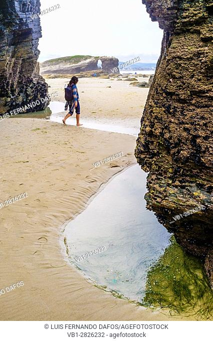 Female solo traveler at Beach of the Cathedrals Natural Monument at Ribadeo municipality, Lugo province, Galicia, Spain, Europe