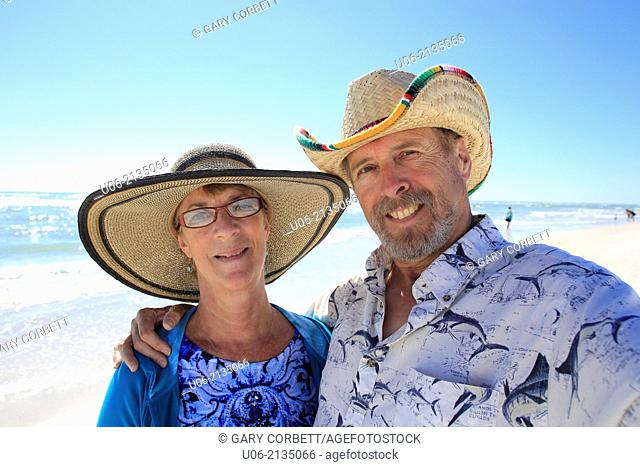 a senior couple smiling for the camera at a beach