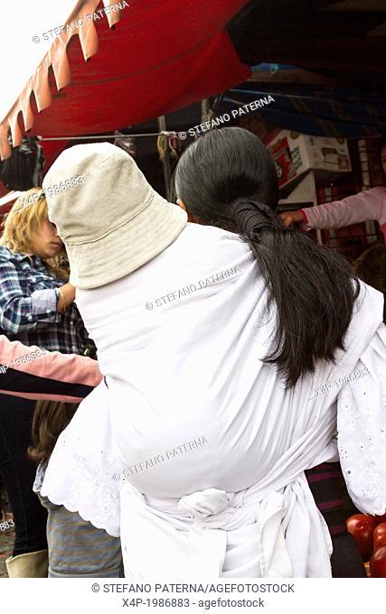 Woman carrying her child, Saturday Market, Otavalo, Ecuador