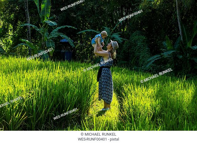 Indonesia, Bali, Ubud, Woman with her baby girl in the rice paddies