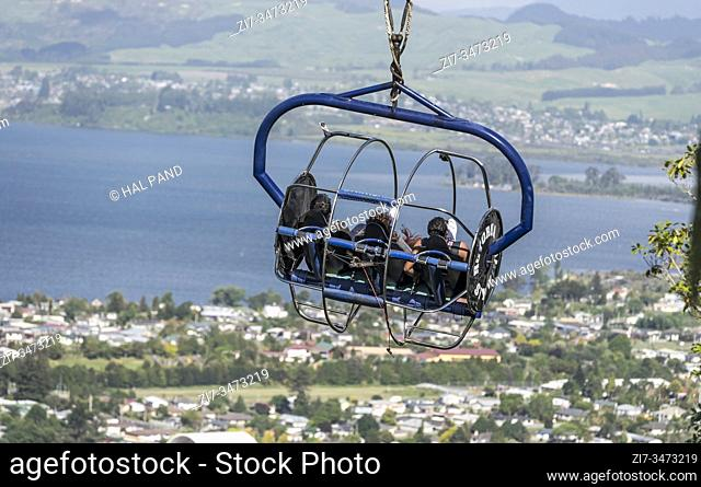 people flyingn in gondola of adrenalinic attraction at park on hill with view on lake and town, shot in bright late spring light on november 09 2019 at Rotorua