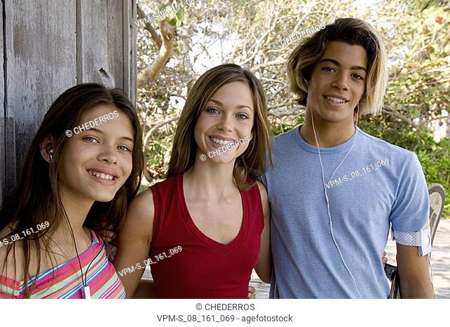 Portrait of two teenage girls and a teenage boy smiling