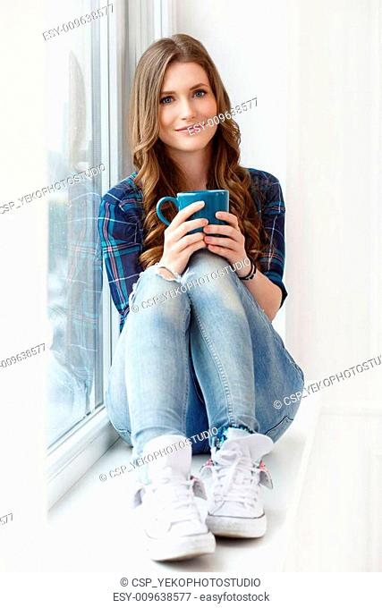Attractive girl by the window