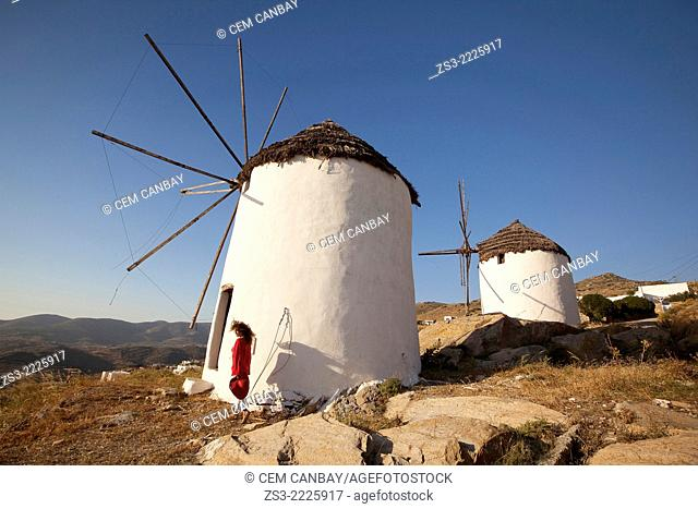 Woman in front of old windmills in town center Chora, Ios, Cyclades Islands, Greek Islands, Greece, Europe