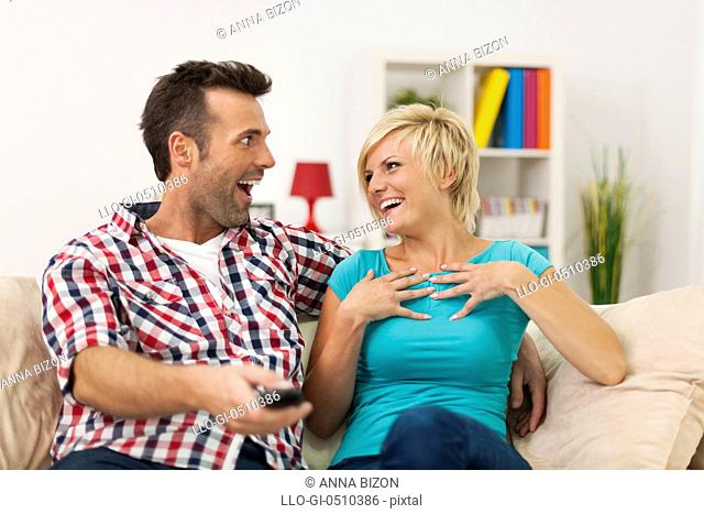 Laughing couple spending time at home with funny movie. Debica, Poland