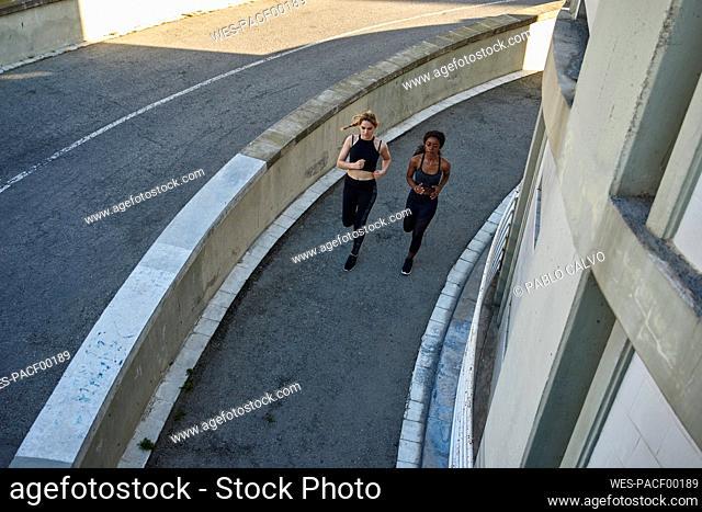 Two sportswomen jogging in the city