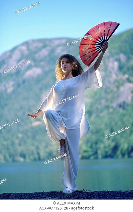 Young woman practicing Tai Chi with a red fan in a Crane, one-leg standing stance at the mountain lake shore in the morning nature