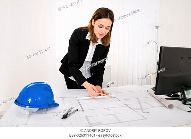 Young Happy Female Architect Working On Blueprint In Office