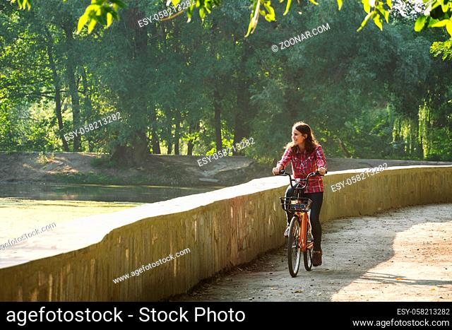 Subject ecological bicycle transport. Young Caucasian woman riding on a dirt road in a park near a lake renting an orange-colored bike in autumn in sunny...