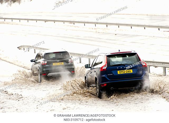 Tredegar, Blaenau Gwent, Wales, UK. 4th March, 2018. Vehicles negotiate a large area of flooding caused by melting snow, on a a slip road leading onto the A465...