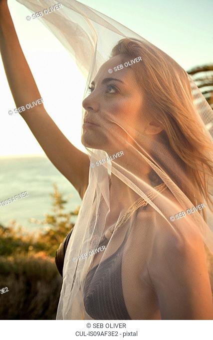 Woman in bikini holding up sheer scarf