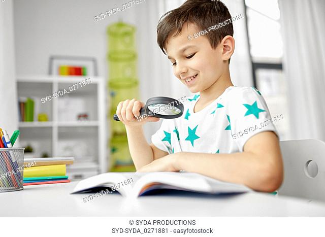 boy with magnifier reading book at home